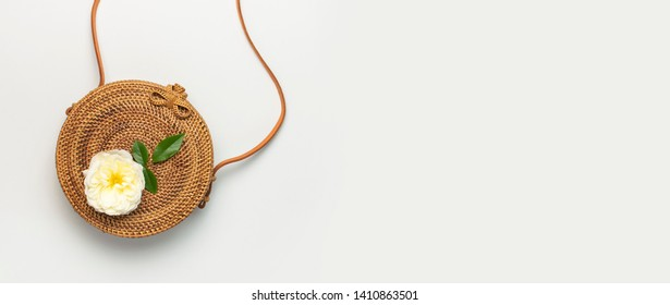 Fashionable concept of women's handbags. Handmade natural organic rattan bag and delicate rose flowers with green leaves on light background. Flat lay, Copy space, top view. Ecobags from Bali.