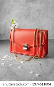 fashionable coral red Crossbody bag on the gray concrete background. crossbody bag made of sheepskin and cowhide leather, a metal clasp, golden chain shoulder strap