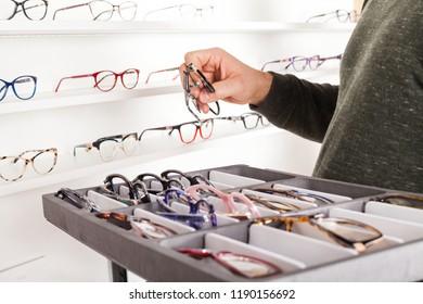Fashionable corrective eye glasses on a shelf in optical store