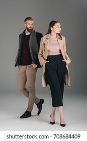 fashionable couple in autumn coat and jacket posing isolated on grey