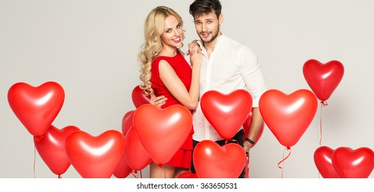 Fashionable couple with balloons heart hugging at each other