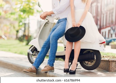 Fashionable couple posing on the street, siting on scooter , wearing stylish casual clothes, black hat and  white dress.Vintage  soft toned colors. Fashion details.