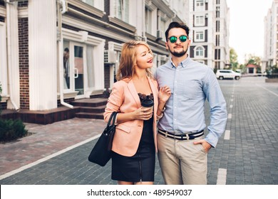 Fashionable couple is walking on street in city. Handsome bearded guy in sunglasses is hugging girl and looks far away. Pretty blonde girl in black dress is talking and smiling to him