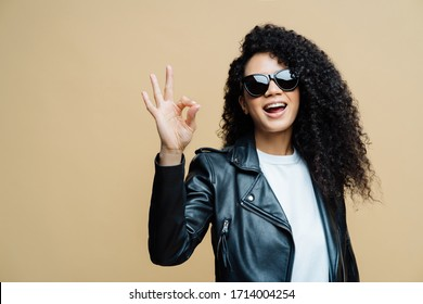 Fashionable curly haired woman tells all is fine, makes okay gesture, says yes to new opportunities, wears trendy sunglasses and black leather jacket, isolated on brown background. Body language