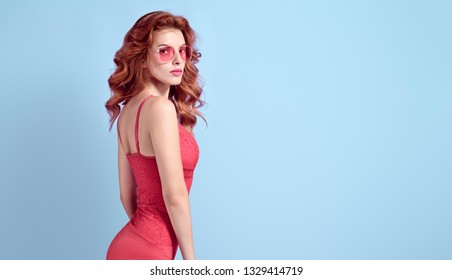 Fashionable Curly Redhead woman with make up wearing Stylish Coral bodysuit. Beautiful sexy fitness Lady in Trendy lace Attire, fashion Sunglasses. Romantic model in Studio. Banner