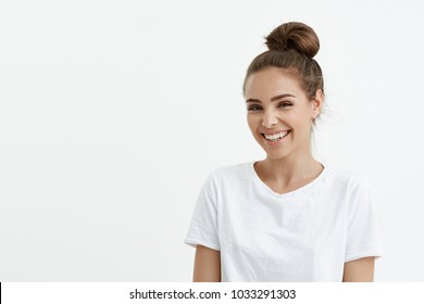 Fashionable cute european female with bun smiling broadly and glancing at camera while standing over white background. Stylish fitness trainer explains how to lose weight without harm for health