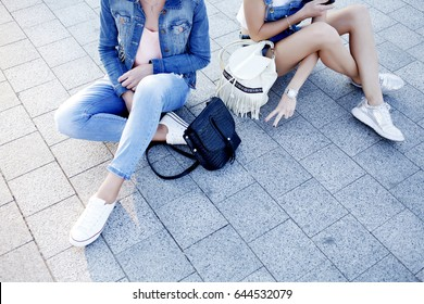 Fashionable details: denim clothing, stylish leather bags and backpacks, sneakers, fashion season spring-summer. Two young hipster girl in trendy outfit, street style.