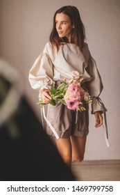 Fashionable details wide sleeves. Woman walking indoors with bouquet or eustoma. The woman in shorts and shirt. Model wearing casual outfit. Summer, spring or fall street look.