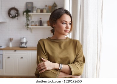 Fashionable dreamy young woman with dark gathered hair standing by window in blurred kitchen interior, keeping arms folded, having pensive facial expression, looking outside, contemplating or dreaming