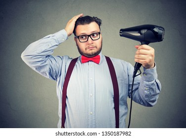 Fashionable eccentric man in glasses drying his hair
