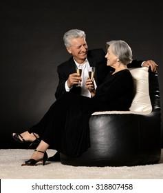 Fashionable elderly couple in studio on black background