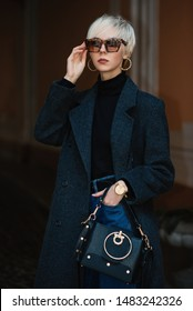 Fashionable, elegant lady with short blonde hair wearing classic gray coat, black turtleneck, sunglasses with animal, leopard print, hoop earrings, wrist watch, holding leather bag, posing in street