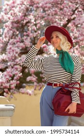Fashionable, elegant woman wearing trendy striped longsleeve shirt, trousers, green neckscarf, marsala color hat, holding big leather handbag, posing in street. Spring fashion, lifestyle concept