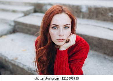 Fashionable emotional close up portrait of a natural beauty ginger girl with freckles on face with long hair posing outdoors on grey background