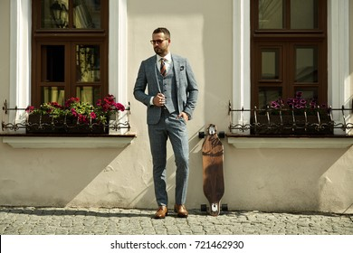 Fashionable European business man in perfect suite walk on the street, using skateboard longboard and sute man