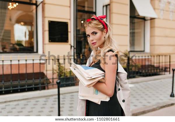 Fashionable european girl with red ribbon in hair looking with gently smile. Lightly-tanned blonde woman in black dress walking to restaurant with newspapers.