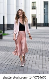 fashionable european girl walks down the street. Skirt plise, long jacket, sneakers. Beautiful long wavy hair. Peach, coral color clothes.