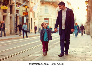 fashionable father and son walking in old city street