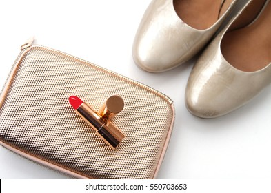 Fashionable female accessories in golden color:  lipstick, clut?h