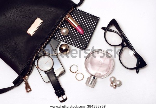 Fashionable female accessories watch glasses lipstick perfume and black bag. Overhead of essentials for any girl