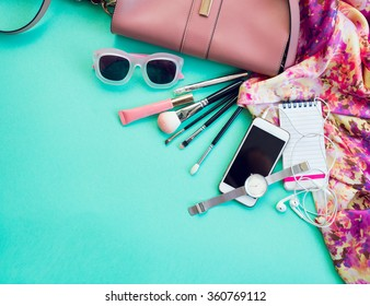 Fashionable female accessories watch sunglasses lipstick  pink  clutch and mobile phone. Overhead of essentials for stylish young woman. Different objects on blue  background . Bright summer colors.