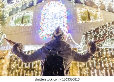 Fashionable female enjoying christmas spirit in front of house with beautiful holiday decoration.