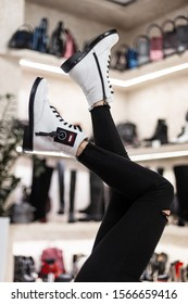 Fashionable female legs in the air in stylish white boots and in black vintage jeans. Modern girl in a shoe store chooses autumn-winter boots. New trendy collection of women's footwear. Close-up.