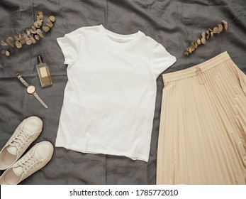 Fashionable female look with white empty t-shirt, cream pleated skirt and white sneakers. Top view of white blank t-shirt with short sleeves over gray bed linen. Mock up for t-shirt print design.
