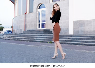 Fashionable female model in black blouse and pencil skirt. Autumn fashion outfit.