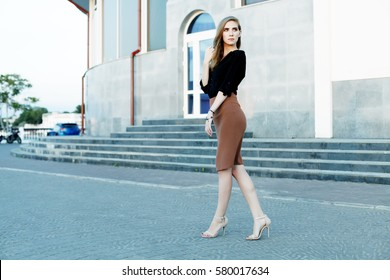Fashionable female model in black blouse and pencil skirt. Spring fashion outfit.