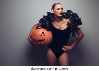 Fashionable female model holding halloweens pumpkin. Studio shot