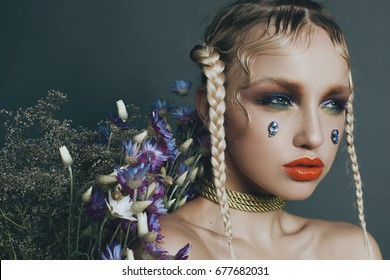 Fashionable female portrait in studio with hair, make-up and flowers