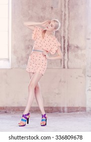 Fashionable full body portrait of blond woman in pink dress.