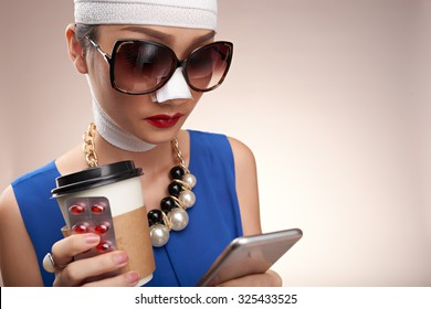 Fashionable girl with bandage on her face reading message in her smartphone