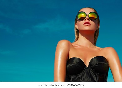 Fashionable girl with a beautiful tan is against the blue clear sky. Girl dressed in a black corset and gold pants. A woman in model pose outdoors. Gold ornaments.