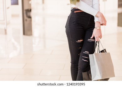 Fashionable girl with blonde haircut walking around at big well-litt shopping centre, choosing gifts for her friends and close people on Christmas day, feeling excited and happy.