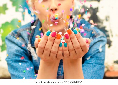 Fashionable girl with bright colorful nail designs blows confetti in her hands.Nails art.Color manicure.