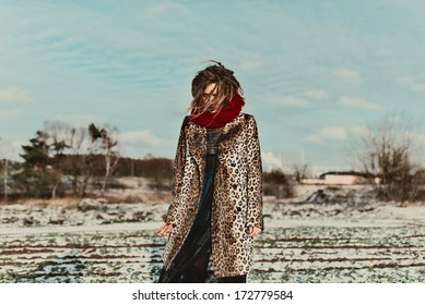 Fashionable girl with dreadlocks in leopard coat for winter field