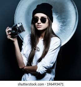 Fashionable girl hipster glasses and a hat in the studio