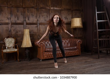 fashionable girl indulges and entertains herself in Loft style interior. model dances in the Urban apartment.
