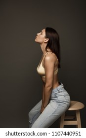 Fashionable girl in jeans and a bra isolated on a gray background.