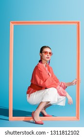 fashionable girl in living coral clothing and sunglasses posing with big frame on blue