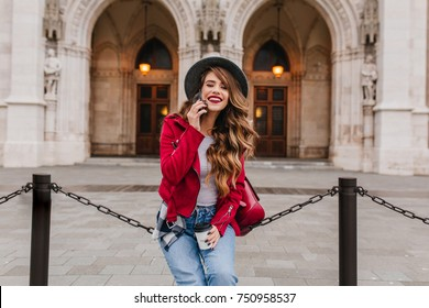 Fashionable girl with long hairstyle talking on phone near amazing historical building in weekend. Outdoor photo of brunette caucasian lady with cup of tea posing on beautiful architecture background.