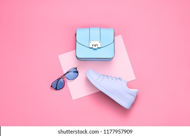 Fashionable Girl Outfit. Woman Accessories Set. Minimal Creative Hipster Flat lay. Fashion sneakers shoes, Trendy purple Handbag, Glamour blue Sunglasses on pink