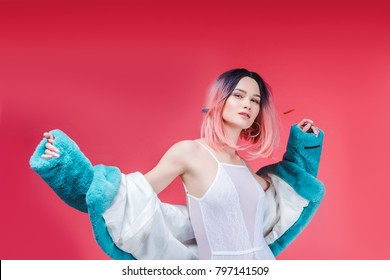 fashionable girl with pink hair posing in lace bodysuit and blue fur coat, isolated on pink