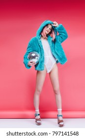 fashionable girl posing in blue fur coat with disco ball on pink