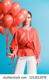 fashionable girl posing with living coral balloons isolated on blue