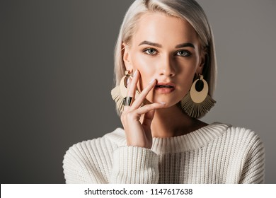 fashionable girl posing in white sweater and round earrings, isolated on grey