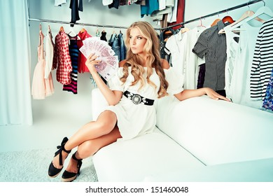 Fashionable girl sitting with a bundle of money in a store. Shopping.