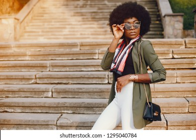 Fashionable girl in a summer city. Black lady in a green jacket. Woman in a red scarf. Famale with sunglasses
